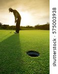 golfer putting golf ball on the ... | Shutterstock . vector #575003938