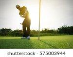golfer putting golf ball on the ... | Shutterstock . vector #575003944