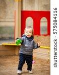 small boy playing in a sandbox. ... | Shutterstock . vector #575084116
