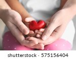 Small photo of Child and adult person holding small red heart, closeup. Adoption concept