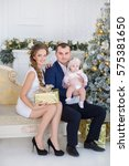 Small photo of Happy family celebrating Christmas all together with cute baby daughter.Handsome father dad and beautiful mother mom with cute baby in wonderful airy fairy dresses celebrating New Year.