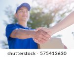 deliveryman stand and shake... | Shutterstock . vector #575413630