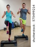 Small photo of Smiling man and woman doing step aerobic exercise on stepper in fitness studio