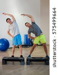 Small photo of Portrait of two men doing aerobic exercise with stepper on fitness studio