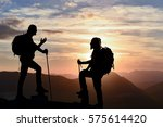 climbers silhouette on top of a mountain at sunset