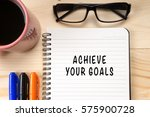 Small photo of ACHIEVE YOUR GOALS on notebook with cup of coffee and glasses on wooden background.
