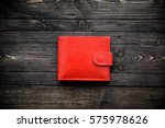 Red leather wallet on wooden background top view
