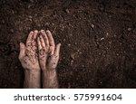 man  farmer's  hands on soil...