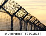 barbed wire steel wall against... | Shutterstock . vector #576018154
