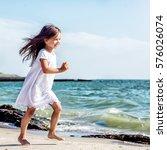 happy little girl on the beach   Shutterstock . vector #576026074