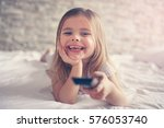 little girl watching tv lying... | Shutterstock . vector #576053740