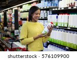 Small photo of Woman looking milk bottle in dairy section of supermarket