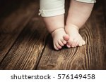 baby feet doing the first steps.... | Shutterstock . vector #576149458