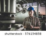 man wearing blue hardhat using... | Shutterstock . vector #576154858