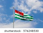Small photo of A huge Abkhaz flag flies in the wind against the blue sky.