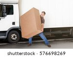 a delivery man or mover holding ...