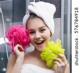 Small photo of Beauty yang smiling girl with pink and yellow wisp in white towels in grey bathroom after shower