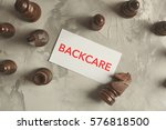 Small photo of Paper with word BACKCARE and chess pieces on gray background