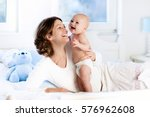 mother and child on a white bed.... | Shutterstock . vector #576962608