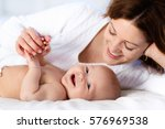 mother and child on a white bed.... | Shutterstock . vector #576969538