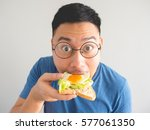 Asian Man Eat Sandwich With...