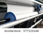 Small photo of Close-up view of paper roll mechanism of professional wide format printer with white paper loaded inside
