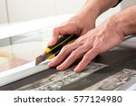 Small photo of Close-up hands of male professional cutting wide format prints using utility knife cutter