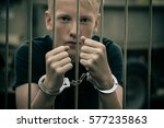 Small photo of Handcuffed teenage boy behind bars in a prison cell staring intently at the camera unrepentant of his criminal behavior