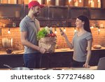 Small photo of Food delivery service. Young man bringing fresh food. Young woman paying with credit card. Nice loft kitchen interior with light bulbs