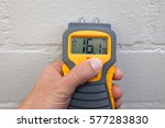 Small photo of A male hand holding a yellow moisture meter in front of a wall
