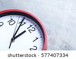 red round clock on a grey...