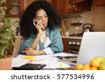 Stock photo sad african female with afro hairstyle sitting in kitchen in front of laptop talking on mobile 577534996