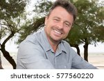 middle aged man smiling outdoors | Shutterstock . vector #577560220