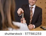Stock photo smiling hotel manager handing over a door key to a woman customer after checking her in to the 577581253