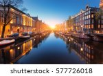 Stock photo colorful cityscape at sunset in amsterdam netherlands reflected city lights in water with blue 577726018