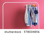 Stock photo hangers with colourful clothes on pink background 578034856
