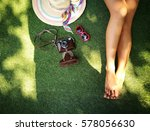 Small photo of Woman leg with camera and hat with copy space ,summer concept