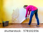 woman repairing a wall in... | Shutterstock . vector #578102356