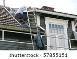 Man on a roof painting the arch of his house - stock photo