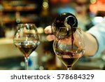 Small photo of Red wine pouring into a wine glass. Shallow depth of field.
