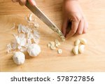 Woman Chopping Garlic On Woode...