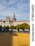 Small photo of Seville cathedral Giralda tower from Alcazar of Sevilla Andalusia Spain. The Alcázar of Seville is a royal palace in Seville, Spain, originally developed by Moorish Muslim kings.