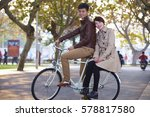 happy young asian couple on bike | Shutterstock . vector #578817580