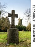 Small photo of stone cross in an old park or gravestone in a cemetery, memorial day symbol for war dead, christian holidays like good friday, easter or pentecost, also used for halloween, vertical