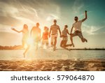 friends jumping on the beach... | Shutterstock . vector #579064870
