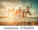 friends jumping on the beach...   Shutterstock . vector #579064870