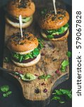 Small photo of Healthy vegan burgers with beetroot and quinoa patty, arugula, avocado sauce, wholegrain bun on rustic wooden board over dark background, selective focus, copy space. Vegetarian, dieting food concept