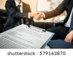 Small photo of Close-up of business contract with pen at workplace on background of office workers interacting. Firm handshake between two colleagues after signing a contract.