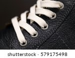Small photo of Close-up of shoelace and eyelets on an aglet of a black shoe