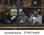 Stock photo friends drinking coffee and chatting in cafe 579474469